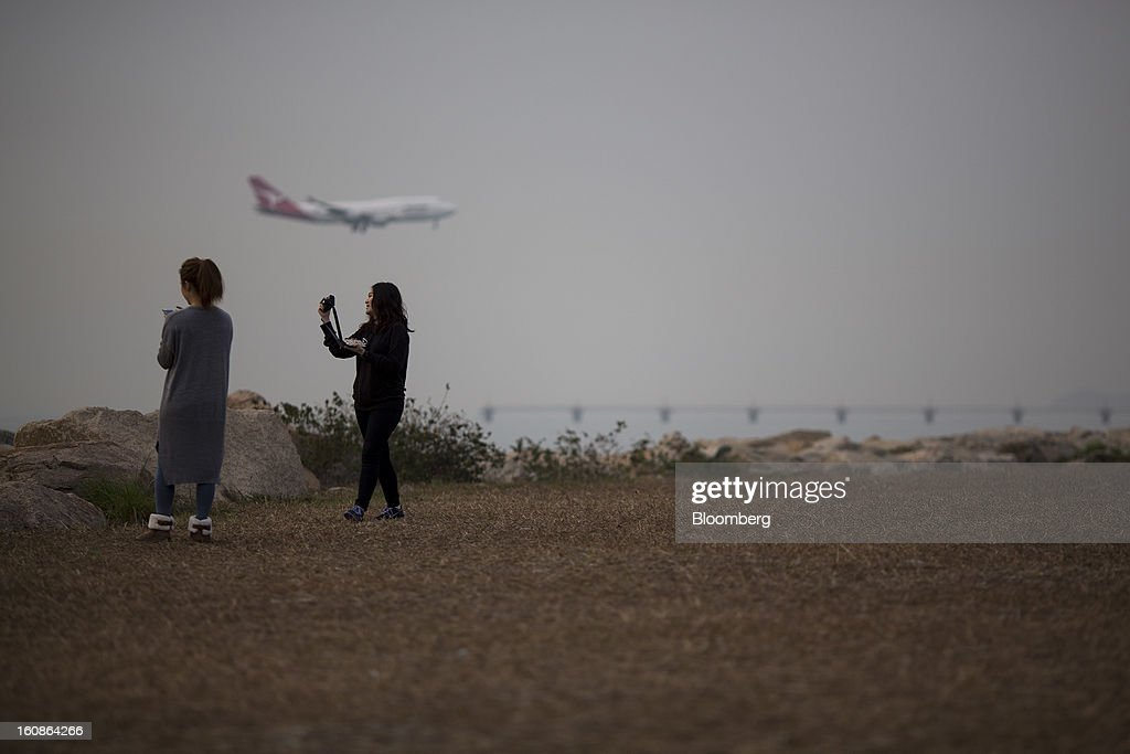 Two women take photographs as a Qantas Airways Ltd. passenger aircraft approaches to land at Hong Kong International Airport in Hong Kong, China, on Monday, Feb. 4, 2013. Cathay Pacific Airways Ltd. aims to replicate its business-class strategy in a cargo trade upgrade. Photographer: Jerome Favre/Bloomberg via Getty Images