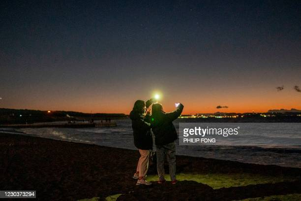 Two women take pictures as they wait at Southern Beach of Chigasaki for the sunrise on New Year's Day in Kanagawa Prefecture, southwest of Tokyo on...