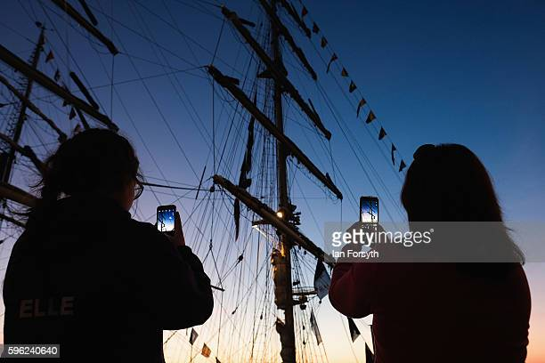 Two women take pictures with their phones of a ships mast during the North Sea Tall Ships Regatta on August 27 2016 in Blyth England The bustling...