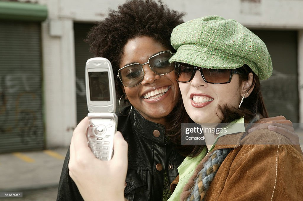 Two women taking a picture with camera phone : Stockfoto
