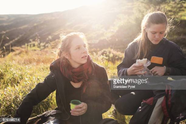 Two women taking break during trekking in mountains at sunset