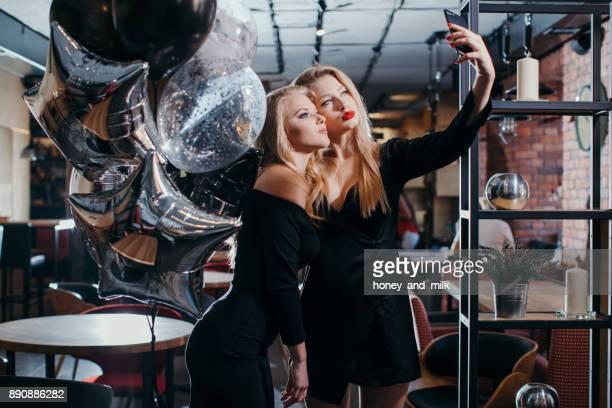 two women taking selfies in a cafe - vestido de cóctel fotografías e imágenes de stock