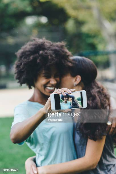 Two women taking selfiewith smartphone in a park