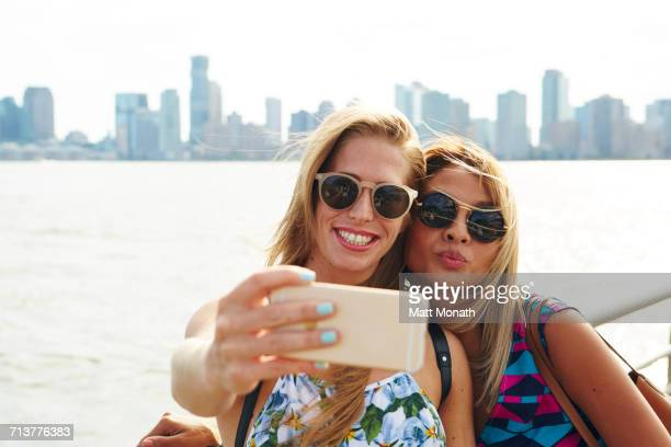 Two women taking smartphone selfie on waterfront with skyline, New York, USA