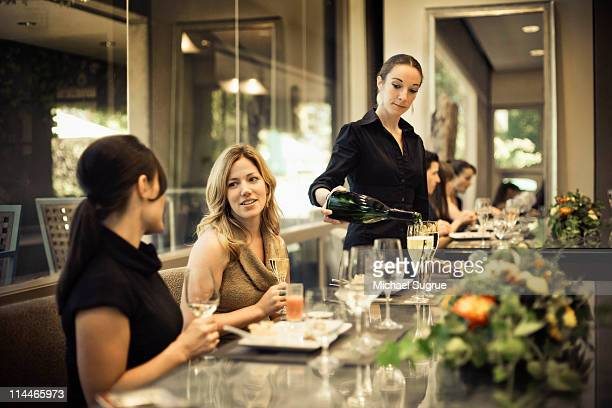 Two women talk at a restaurant table.