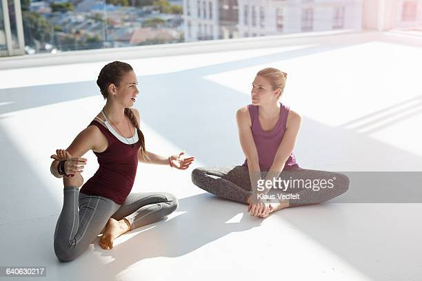 Two women talking and streching in yoga studio
