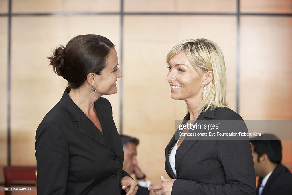 Two women talking during business meeting in hotel lobby : Stock Photo