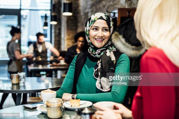 two women talking in cafe with drinks and food - headscarf stock pictures, royalty-free photos & images