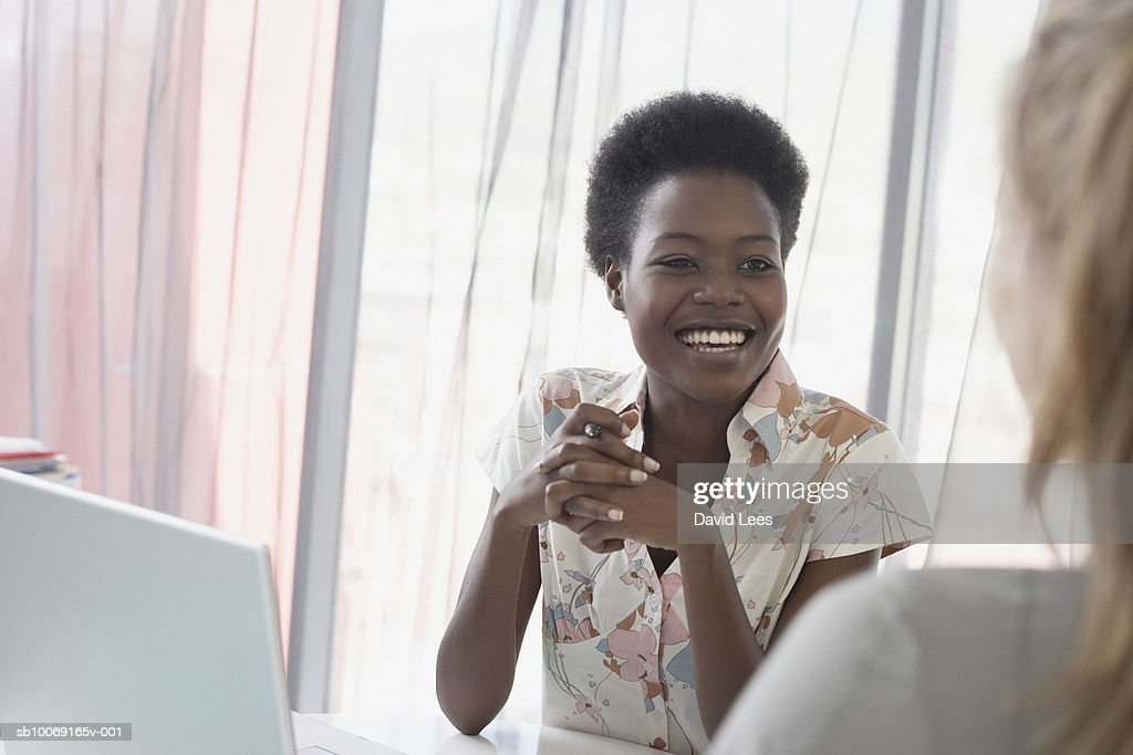 Two women talking in office : Stockfoto
