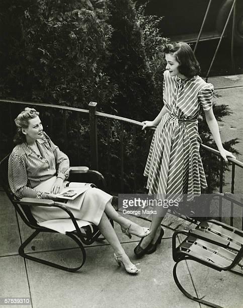 Two women talking on balcony, (B&W), elevated view
