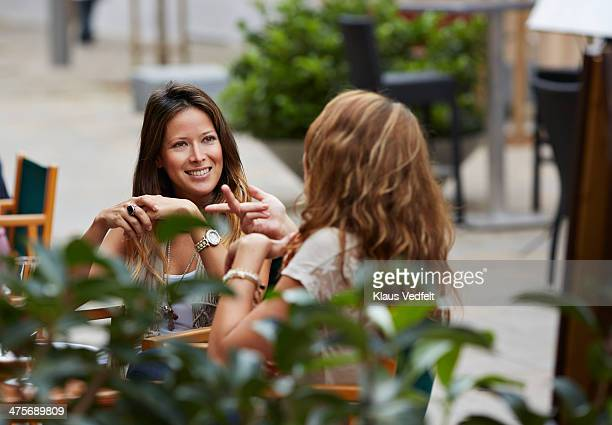 two women talking together at restaurant - klaus vedfelt mallorca stock pictures, royalty-free photos & images