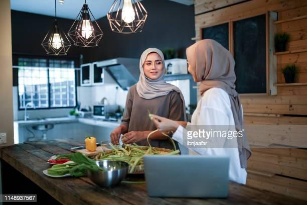 two women talking while preparing food - eid mubarak stock pictures, royalty-free photos & images