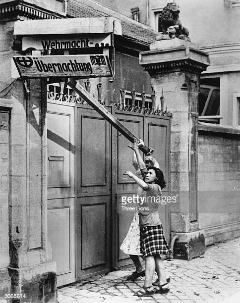 Two women tearing down a sign in front of Nazi headquarters in Troyes, France.