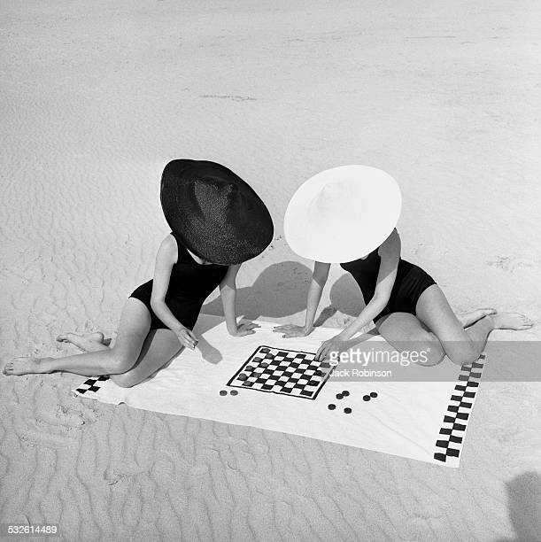 Two women, their faces obscured by fashionable hats, play checkers on the beach, 20th century.