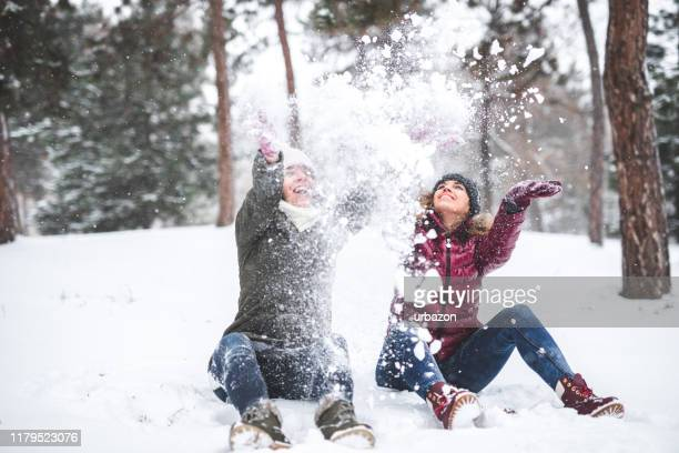 two women throwing snow - february stock pictures, royalty-free photos & images