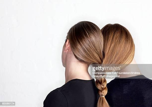 two women tied together by hair plait - frau gefesselt stock-fotos und bilder