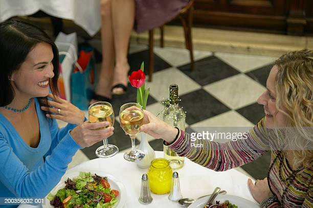 Two women toasting each other with wine in restaurant, smiling