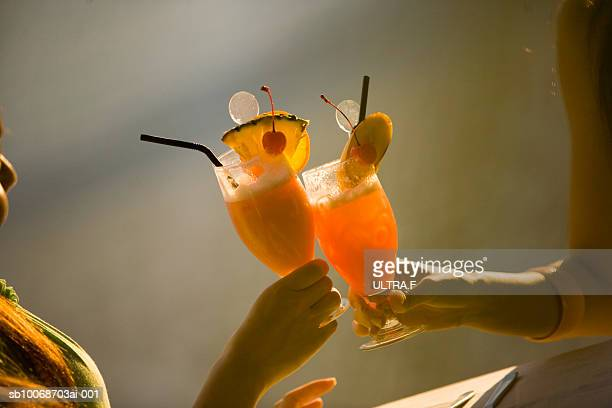 Two women toasting with cocktails, close-up of hands