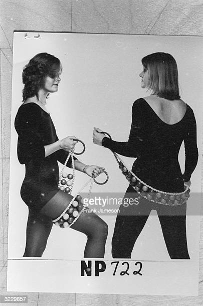 Two women toning their muscles with a 'Rollertone' massage belt