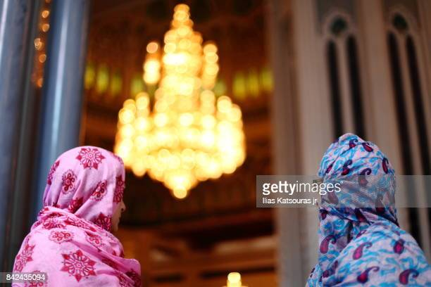 two women tourists in bright headscarves in the main praying hall of the sultan qaboos grand mosque, with chandelier in the background - crystal mosque stock pictures, royalty-free photos & images