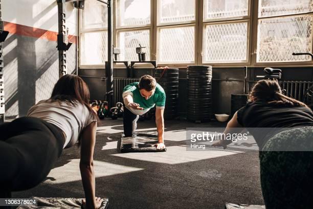 due donne che si allena con istruttore di fitness - solo adulti foto e immagini stock