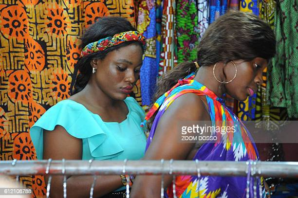 Two women try clothes at an African clothes shop in Monrovia on September 6 2016 After almost 200 years of Western influence on their clothes...