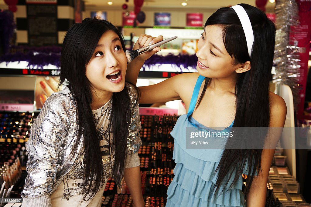 Two women trying on makeup in retail store : Stock Photo