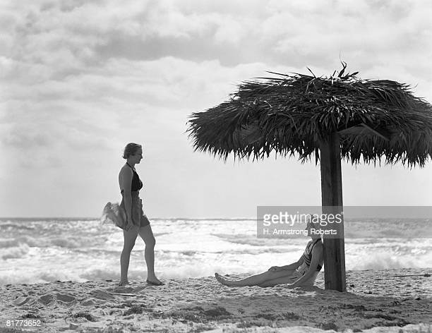 Two women under palm thatch umbrella on beach, Florida.