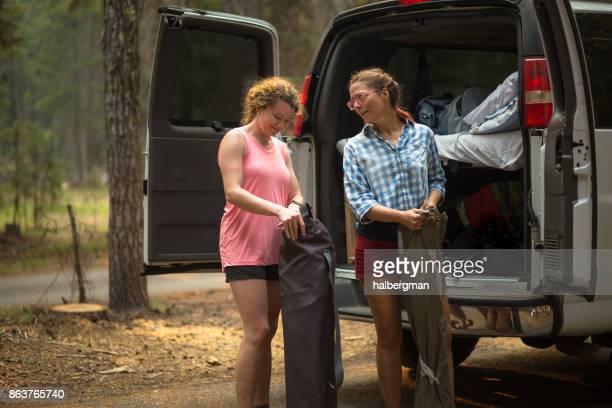 Two Women Unloading Camping Gear from Van