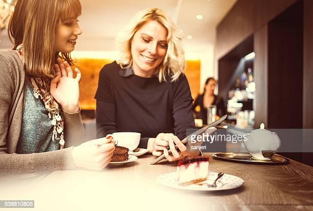 デジタルタブレットを使用して 2 つの女性のコーヒーショップ