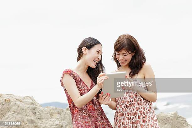 Two women using digital tablet in beach,smiling