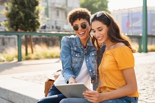 Two women using digital tablet outdoor 1134003590