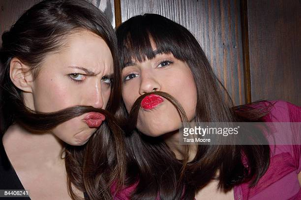 two women using hair as moustaches