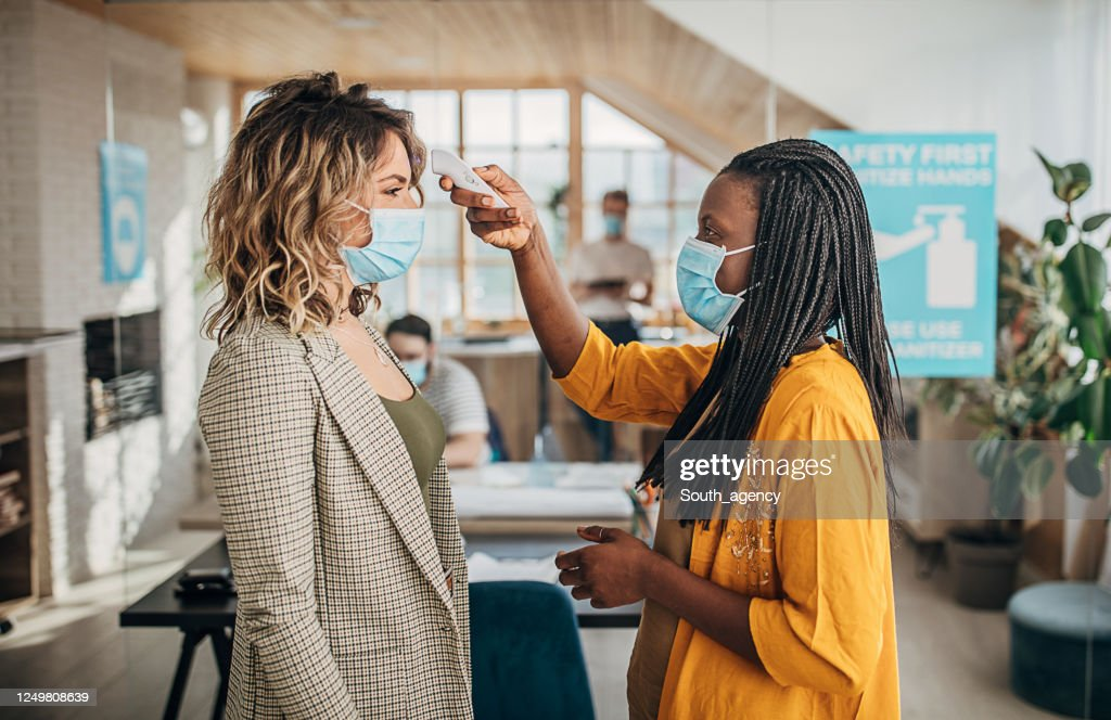 Two women using infrared thermometer for measuring temperature before entrance in office : Stock Photo