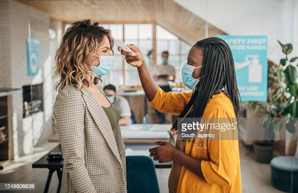 two women using infrared thermometer for measuring temperature before entrance in office - coronavirus stock pictures, royalty-free photos & images