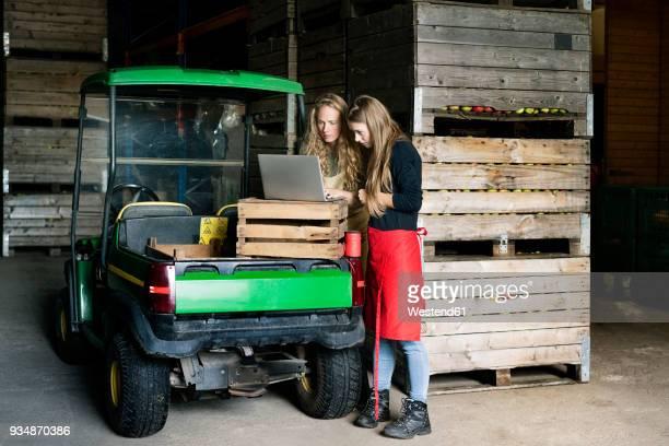 two women using laptop between crates on a farm - food truck stockfoto's en -beelden