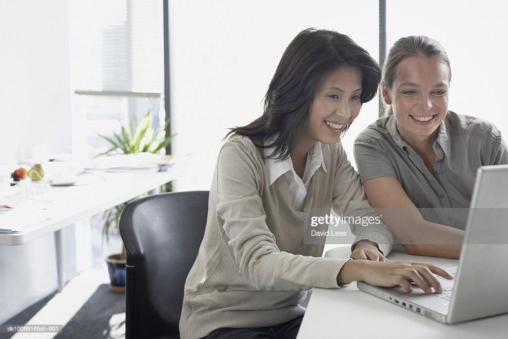 Two women using laptop in office : Stockfoto