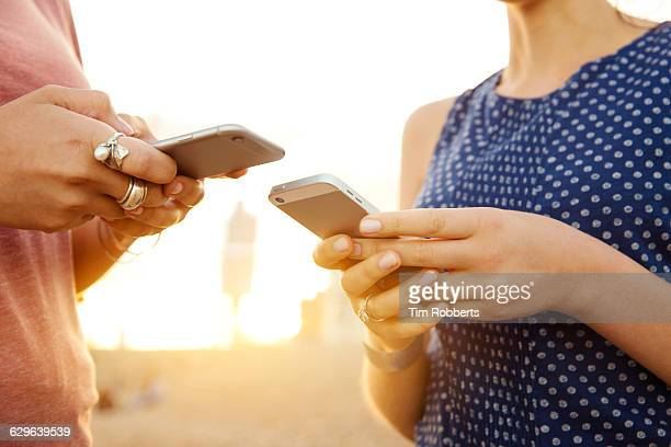 two women using smart phones, close up. - zwei personen stock-fotos und bilder