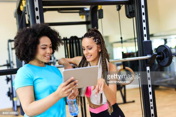 Two women using tablet in gym