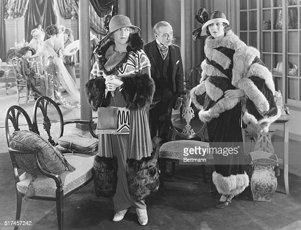 Two women visiting a dress salon donning styles of the late 1900s including broadbrimmed ribboned hats fur trimmed cloaks over anklelength slimlined...