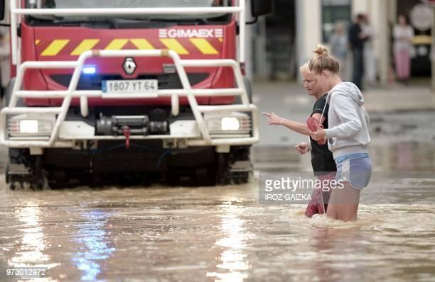 Two women wade through flood waters following heavy rains in SaliesdeBearn south western France on June 13 2018