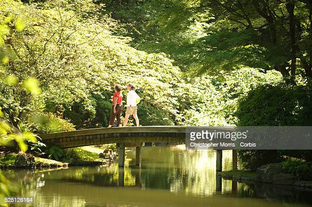 Two women walk across a bridge in the Nitobe Gardens, the Japanese garden is located on the University of British Columbia campus.
