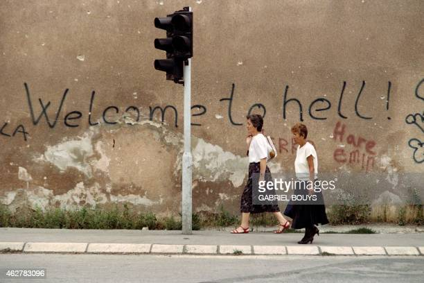 """Two women walk across the area of Sarajevo known as """"Sniper Alley"""" on August 24 1993, near a wall with graffiti that reads """"Welcome to Hell."""" The..."""