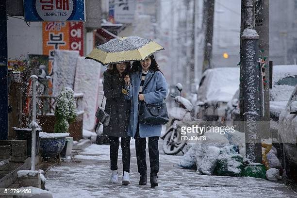 Two women walk along a street beneath an umbrella during snowfall in Seoul on February 28 2016 AFP PHOTO / Ed Jones / AFP / ED JONES