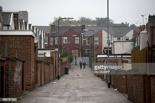 Two women walk along an alley between terraced houses in Rotherham South Yorkshire North England on October 6 2014 An inquiry revealed on August 26...