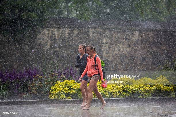 Two women walk barefoot through heavy rain in Westminster on June 8 2016 in London England The Met Office has issued flood alerts for parts of the...