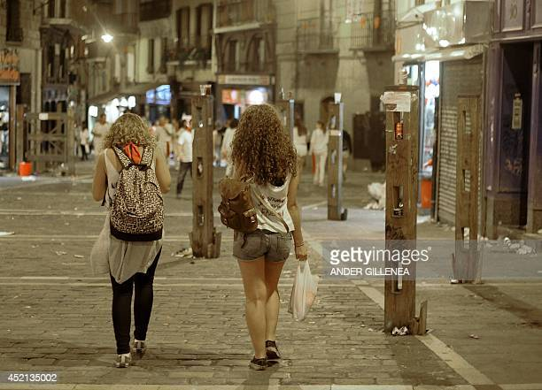 Two women walk down Mercaderes street littered with plastic glasses and cans during the San Fermin Festival in Pamplona northern Spain on July 13...