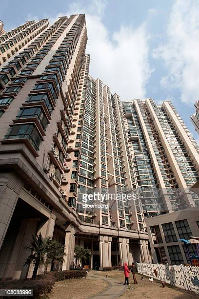 Two women walk in front of a housing complex in Shanghai China on Monday Jan 17 2011 Shanghai China's financial center will this year prepare for a...
