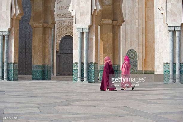 two women walk in hasan ii mosque in casablanca, morocco - casablanca stock pictures, royalty-free photos & images