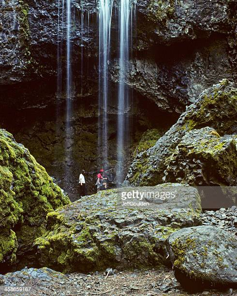 Two Women Walking Behind a Waterfall